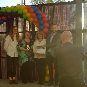 Cris McCurley and Lui Asquith presenting the 'Building a Stronger LGBT+ Community' Award to Northern Proud Voices